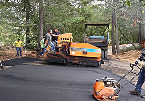 R & R Paving crew paving a driveway in a wooded area