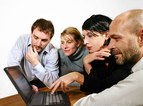 4 business people looking at a laptop